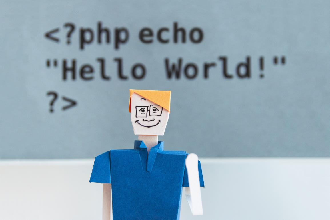 "White man paperdoll ith code overhead that says ""Hello World!"""