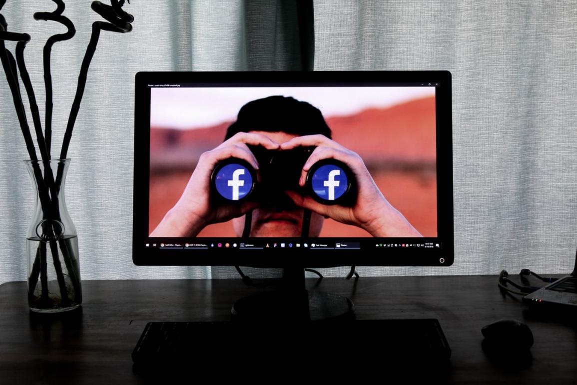Image of a computer monitor with someone holding binoculars that have the Facebook logo