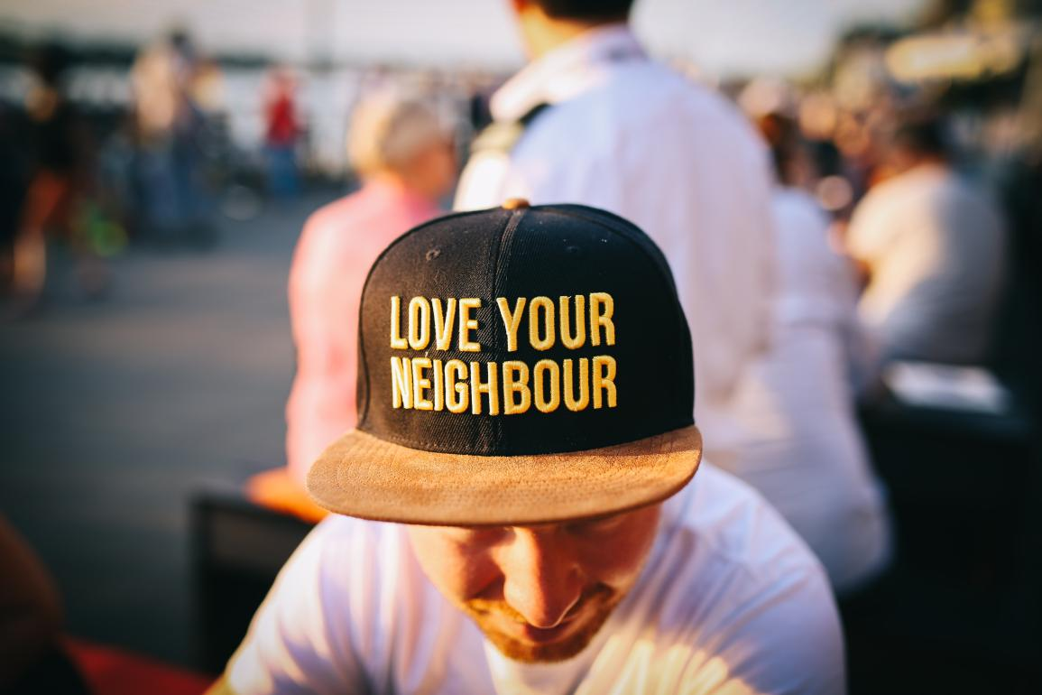 "Man wearing hat that says ""Love Your Neighbour"""